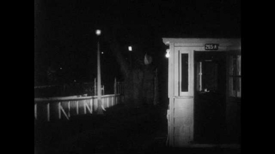 1950s: UNITED STATES: guard stands at patrol box. Ladies arrive at gate. Man speaks to lady