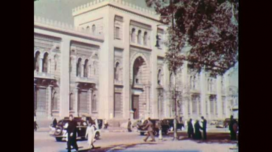 1950s: EGYPT: city buildings in Cairo. Cars in street. People walk past buildings. Bus in Cairo. Modern apartment building in Cairo. Boat on River Nile. Crafts workers in market