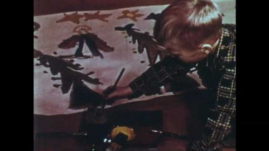 1950s: Boy sits and paints Christmas drawing on paper. Boy sits and cuts notches in paper with scissors.
