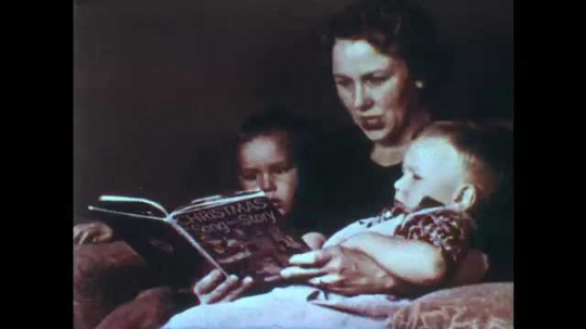 1950s: woman reads Christmas book to children. Boy walks up. Woman takes our present and inspects it.