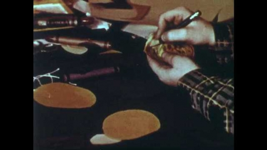 1950s: Boy pokes hole through golden circle and pulls string through hole