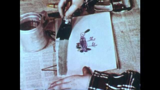 1950s: Boy drags wet black paint across page of paper with picture of turkey. He drags brush across page several times.