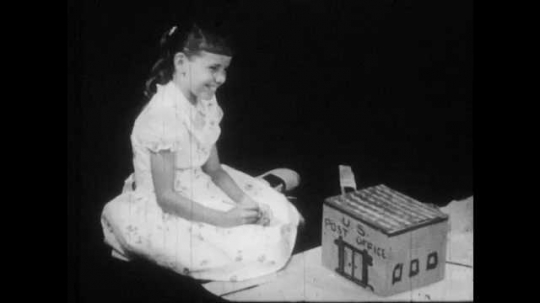1950s: girl sits in front of model post office. girl draws on house. boy plays with cardboard box. girl paints drugstore. Girls and two boys kneel around paper and play as boy stands in darkness.