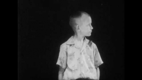 1950s: boy with buzz haircut stands in darkness, looks down at the floor and talks.