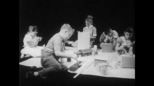 1950s:  three girls and two boys kneel around a large sheet of paper, play with cardboard box houses, paint streets with a brush and talk in a black room.