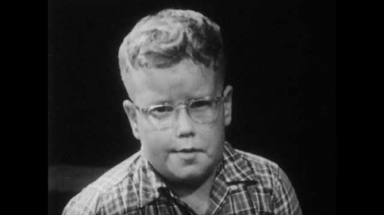 1950s: boy with eyeglasses talks. girl in ponytail nods head. boys and girls sit on floor and speak.