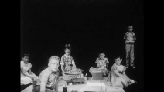 1950s: Girls and two boys kneel around paper and talk and listen as boy with buzz-cut stands in darkness. girl shakes her head.