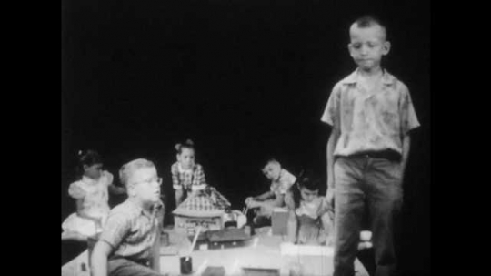 1950s: boy with buzz-cut stands near boys and girls and talks as girl in dress stands up, sticks tongue out, puts hands on hips, sneers, speaks and walks away with nasty stare.