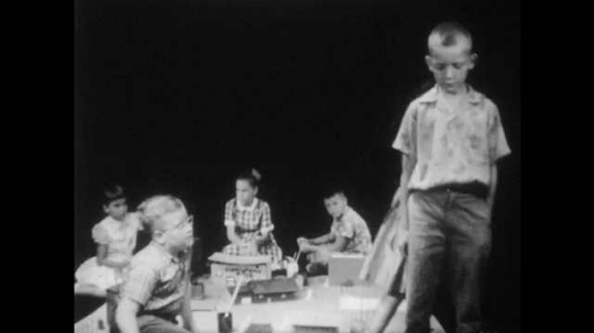 1950s:  boy with buzz-cut and Hawaiian shirt stands near boys and girls, talks, stars down, slouches shoulders, listens and looks upset.