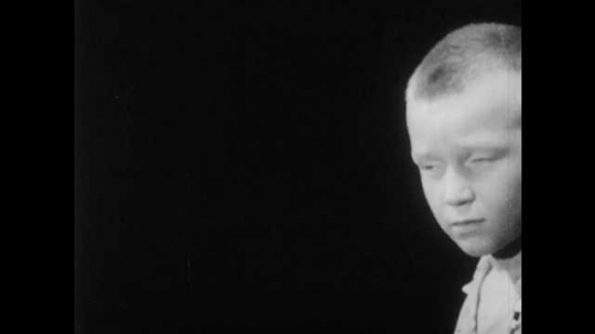 1950s: boy with buzz-cut turns, talks and watches as hand with chalk draws happy and frowning faces on blackboard.