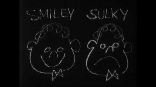 1950s: sulky and smiley heads are on drawn on blackboard as hand erases frown and draws smile on face. boy with buzz-cut looks sad and fights mouth to form smile.