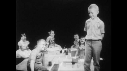 1950s: boy with buzz-cut smiles, kneels down and plays with boys and girls around large piece of paper with cardboard model buildings with paints in dark studio.