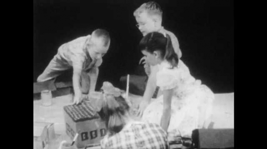 1950s: three girls and three boys kneel around a large sheet of paper, play with cardboard box houses until boy with buzz-cut gets angry, argues and grabs buildings.