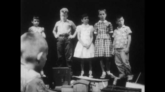 1950s: boys and girls stand in a line, stare down and talk to boy on ground near paper and cardboard building models. girl kneels down and ties shoelaces on saddle shoes.