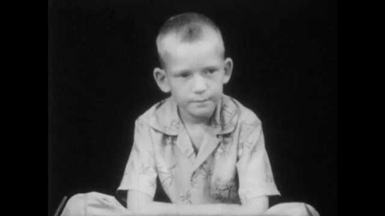 1950s: boy with buzz-cut and Hawaiian shirt sits on floor, talks and listens. hands ties shoelaces on saddle shoe.