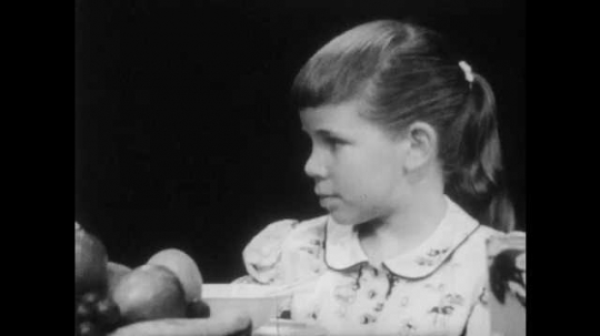 1950s: man, boy, woman and girl sit at kitchen table, talk and listen as family points at heads with fingers. girl with ponytail gestures at forehead.