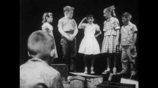 1950s: boys and girls stand in a line, talk, point at heads, stare and step forward as boy with buzz-cut and Hawaiian shirt sits on floor and listens and replies.
