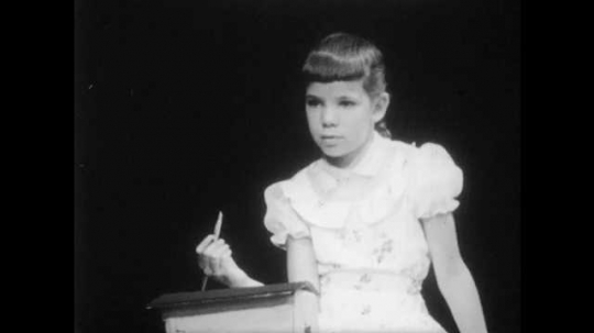 1950s: girl sits, holds paintbrush, smiles and points at head. boy with buzz-cut returns brush, pushes model, touches forehead, and moves building as boys and girls look happy. kids draw with crayons.