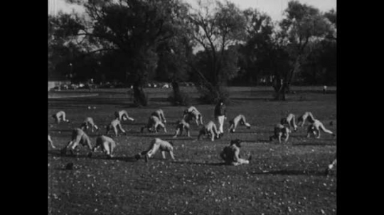 1950s: Football players exercise.  Waitress serves drink.  Man hands teenage boy money.  Students sit in classroom.  Boy sits down and begins work.
