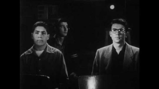 1950s: Boy turns off film projector.  Boys speak.  Boy starts projector.  Students work in classroom.  Teacher walks around room.