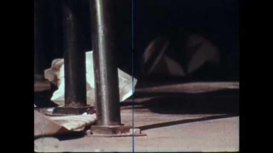 1970s: Close up, broom sweeps trash. Feet step in gum. Cup on ground. Zoom in, kids on swing set.