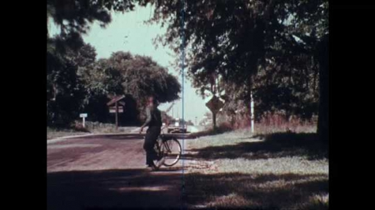 1970s: Boy gets on bike, rides away from camera. Boy and girl walking.