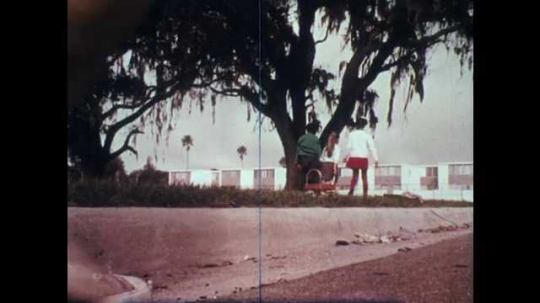1970s: Low angle view, kids pull wagon, throw litter in wagon. Long shot, kids picking up trash.