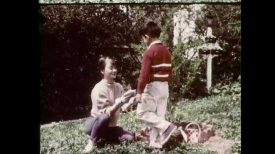 1960s: UNITED STATES: lady in garden with boy. Seeds in hand. Lady plants seeds in soil. Lady covers seeds with soil