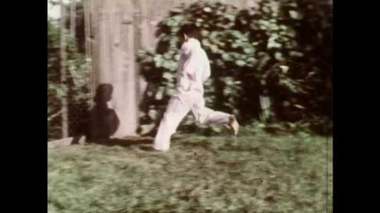 1960s: UNITED STATES: boy runs across garden. Boy checks on seeds. Lady calls to boy in garden