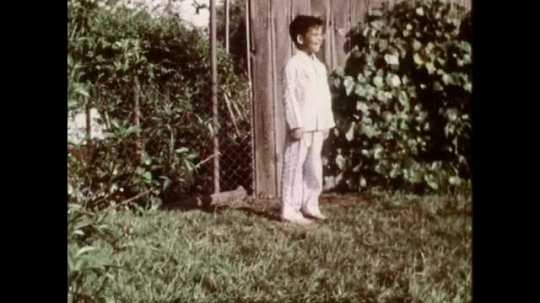 1960s: UNITED STATES: boy runs across garden. Sunshine in garden. Boy skips in garden. Dry soil in garden