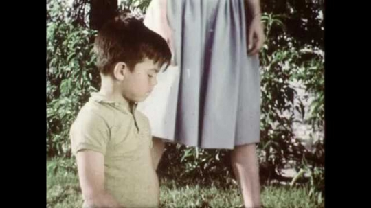 1960s: UNITED STATES: seed in soil. Lady talks to boy in garden. Plants grow in soil. Time lapse of plant growth