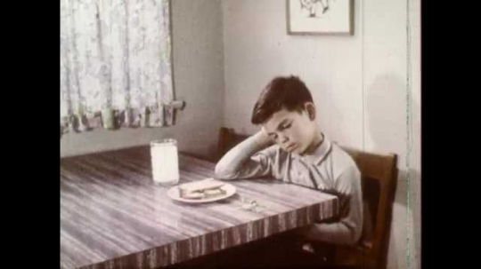 1960s: UNITED STATES: Boy sulks at table. Lady talks to boy. Hands open seeds.