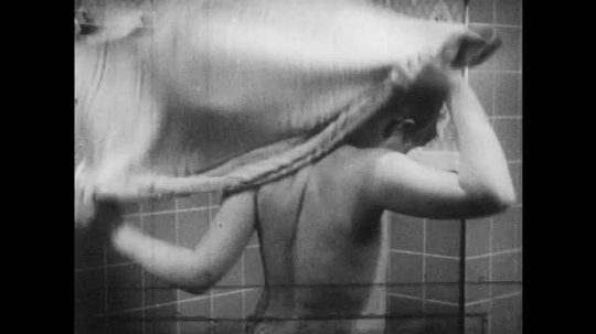 1950s: UNITED STATES: boy dries self with towel in bathroom. Model of human head. Mucus membrane in mouth. Mucus membrane in mouth