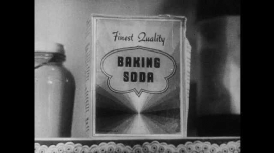 1950s: UNITED STATES: Baking Soda on shelf in box.  Smoke escapes from oven. Lady closes oven door. Lady turns off oven
