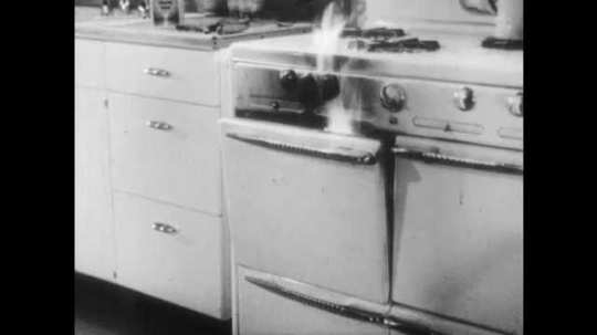 1950s: UNITED STATES: flames escape oven. Lady pours baking soda on flames in oven.
