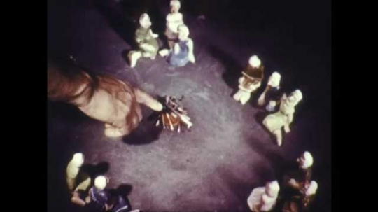 1960s: Groups of figurines sit in circle around fire. Man points. Man moves figurine in circle around fire.