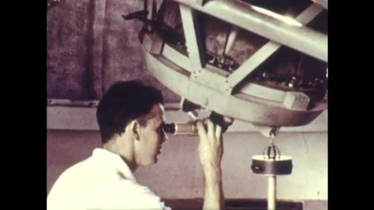 1960s: Observatory, man looks into large telescope, attaches camera to telescope, manipulates parts.