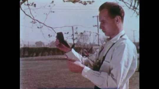 1950s: UNITED STATES: man holds camera light exposure meter. Static needle on monitor. Pylons and wires against sky. Lamp on side in house.