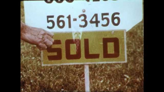 1950s: Man pushes for sale sign into ground in front of house. Man walks back to house.