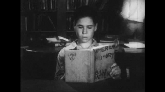 1940s: A boy reads aloud from a book. He follows along in the book with his finger. A librarian checks a book out for a student. She stands to help some other students.