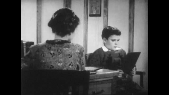 1940s: A boy sits in a chair next to a woman at a desk. He reads silently off a sheet. He looks frustrated and confused.
