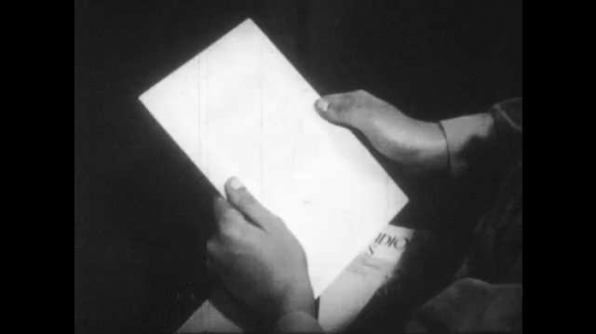 1940s: A boy reads aloud from a sheet. He begins to point at the words on the page, but stops himself. A woman holds her finger to her lips and he bites his lips, then continues to read silently.