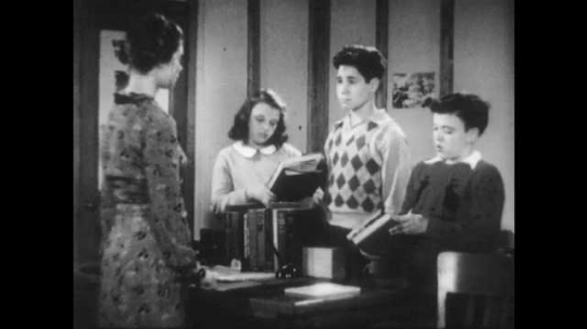 1940s: Three children stand in front of a woman