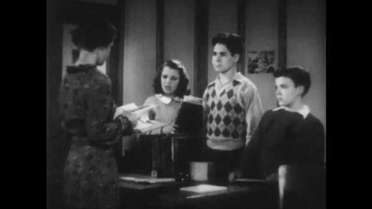 1940s: Three children stand in front of a woman at her desk. She flips through a book and hands it to one of the boys as they all speak with each other.