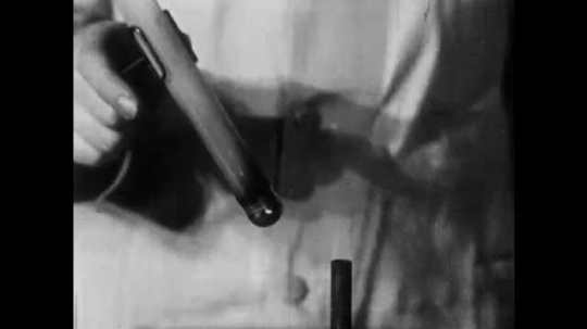 1940s: Scientist cracks open hardened mixture of Sulphur and iron from test tube on bench. Black particulate and matter shatter on to bench.