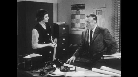 1950s: UNITED STATES: man speaks with colleague in office. Lady speaks with boss.