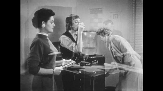 1950s: UNITED STATES: ladies stand by water in office. Ladies speak. Lady drinks cup of water. Lady curls up cup