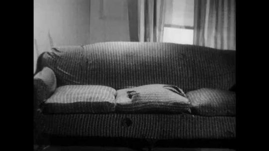 1950s: Couch with ripped cushions. Man walks to couch, kneels down, looks at holes, pushes spring back into hole. Man takes off coat, hangs on coat rack, puts on hat, coat falls of. Man puts on coat.