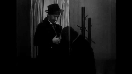 1950s: Man walks around store, looks at furniture, salesman talks to man. Man points at installment plan sign. Salesman and man talk, salesman writes on notepad.