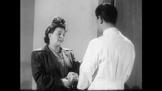 1950s: Woman talks with doctor in doctor's office.
